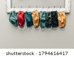 Small photo of A row and variety of colorful protective face masks hanging on a home bulletin type clipboard for going back to work or back to school for easy access with copy space