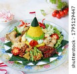 Nasi Tumpeng or cone-shaped rice surrounded by various kinds of Indonesian specialties.  Usually served for events such as Indonesian Independence Day and other events.  With white background.