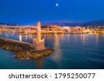 Panorama of the beautiful old harbor of Chania with the amazing lighthouse, mosque, venetian shipyards, at sunset, Crete, Greece.