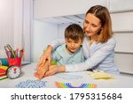 Small photo of Boy with autism learn weather using cards, teacher hold hands and point to correct one