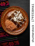 Small photo of Traditional mexican chicken enchiladas with mole sauce and rice on dark background
