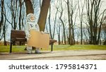 Sad Man in Spacesuit is Sitting on a Bench in a Park and Holding a Carboard Mockup Sign. Miserable Astronaut Looks in the Distance. Emotionally Depressed Spaceman in White Futuristic Suit. - stock photo