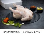Small photo of Raw whole chicken with skin arranged on grill and garnished with parsley,small tomato,spring onion,chilly flakes and lemon slices with stone textured or graphite colour as background,isolated