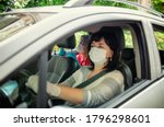 Small photo of Caregiver drives her elder client to planned outings or events. Both wear protective masks. The face of the assistant is slightly blurred, the old woman is in focus.
