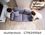 Couple Moving And Carrying Sofa ...