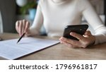 Small photo of Close up focused financier reading paper contract agreement, checking latest investment news in smartphone application indoors, concentrated female editor reading document or report at workplace.