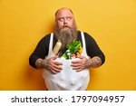 Small photo of Obese greedy man stocks foodstuff, eats too much, suffers from overweight and gluttony, keeps hands on belly full of products, has tattooed arms, thick beard, concentrated with frightened look