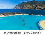 """Small photo of Porto da Cruz, Madeira, Portugal - August 2020: Tourists and local people bathing on """"Porto da Cruz"""" beach in Porto da Cruz, Madeira island, Portugal"""