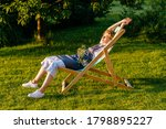 Small photo of Beautiful smiling woman gardener in apron relaxing, stretching in a sun lounger on a grass meadow outdoor. She is absolutely happy. Slow living, gardening hobby concept