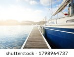 Elegant and modern sailing boats (for rent) moored to a pier in a yacht marina on a clear day. Sweden. Blue sloop rigged yacht close-up. Vacations, sport, amateur recreational sailing, cruise