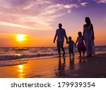 Family Walking On The Beach At...