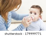 Young Mother Feeding Baby At...