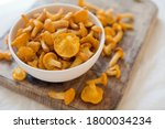 Raw chanterelle mushrooms on a white bowl on wooden background. Food background with yellow mushrooms