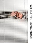 Small photo of Agoraphobia. A man looking through a rain spotted window blinds with facial expressions.