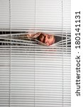 Small photo of Agoraphobia. A man looking through window blinds with facial expressions.