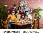 Small photo of Indian family wears face mask while eating food in restaurant after corona pandemic unlock - concept showing new normal lifestyle in India