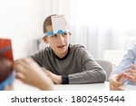 Small photo of Child boy with a card on his forehead. Children playing a game guess who I am. Playing guess sticker. Game Play Friends Fun Guess Entertainment Party