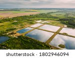 Small photo of Aerial View Retention Basins, Wet Pond, Wet Detention Basin Or Stormwater Management Pond, Is An Artificial Pond With Vegetation Around The Perimeter, And Includes A Permanent Pool Of Water In Its