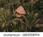 Small photo of Aerial view from drone happy travel couple on hammock balcony of bamboo tree house with jungle nature view. Vacation in beaitiful hidden place, honeymoon on Bali island