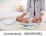 Doctor Weighting Cute Baby In...