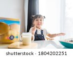 Small photo of Toddler cute little asian girl drinking milk at table in kitchen.Thumb up for good milk.Cute baby girl drinking milk with milk mustache at home.Concept for food, Growth in kid, Child development.