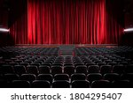 Small photo of Darkened empty movie theatre and stage with the red curtains drawn viewed over rows of vacant seats from the rear