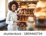 Small photo of Smiling baker woman standing with fresh bread at bakery. Happy african woman standing in her bake shop and looking at camera. Satisfied baker with breads in background. Smiling woman at bakery shop