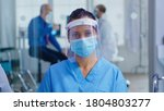 Small photo of Medical assistant with visor and face mask against coronavirus looking at camera in hospital waiting area. Doctor consulting senior man in examination room.