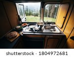 Interior of travel camping van or camper RV with stove and sink. Vanlife lifestyle vibes, cooking on campsite during road trip with amazing view of mountains. Life on the road in converted van - stock photo