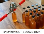 Small photo of Hand capper on the background of brown bottles with homemade liquor or alcohol. Home brewing.