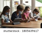 Small photo of Four diverse kids wear facemasks sit at table use wireless gadgets ignoring each other prefer internet games and virtual communication. Alpha generation and modern technology overuse, phubbing concept