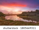 River misty autumn sunrise. Colorful dawn. Cloudy sunrise. Dusk fall colors. Riverbank with grass and bushes. Fog over lake, Belarus - stock photo