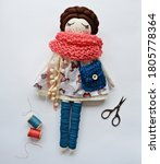 Small photo of Heirloom textile doll with brown hair wearing cute dress, teal gaiters, blue knitted handbag and coral scarf