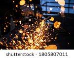 Small photo of Metal processing in the workshop. Grinding metal. The worker makes the structure of a metal profile. Creating a shelving for the city dweller. Sparks from metal friction.
