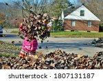 Young Girl Playing In A Pile Of ...