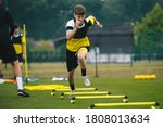 Small photo of Soccer player running fast and ladder skipping. Teenagers on soccer training camp. Boys practice football witch young coach. Junior level athletes improving soccer skills on outdoor training