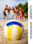 beach volleyball ball at the beach with the team behind - stock photo