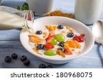 Pouring milk on cornflakes with fruits - stock photo