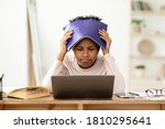 Small photo of Frustrated African Kid At Laptop Getting Bad Grade During Online Class, Covering Head With Exercise-Book Sitting At Home. School Failure