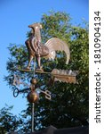 Small photo of Weather vane in the form of a cock on the house roof common name as wind vane or weathercock is an instrument used for showing the direction of the wind.
