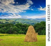 a pair of haystacks and a tree on a green meadow at the foot of the mountain - stock photo