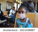 African American Girl wearing mask sitting in subway car