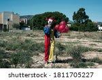 A Creepy Clown Wearing A Yello...