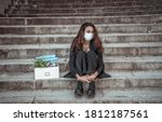 Small photo of COVID-19 lay off and unemployment. Depressed business woman with face mask outside office with personal staff box feeling hopeless after losing job due to redundancy amid Coronavirus job cuts.