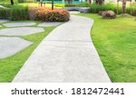 Walkway and bush. That is concrete pavement, floor, passage, path, footpath, pathway or passageway with nature for walking along and connecting different section of a building, park or garden.