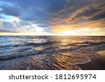 Small photo of Clear sky with lots of dark glowing cumulus clouds above the Baltic sea shore after thunderstorm at sunset. Dramatic cloudscape. Warm golden light. Picturesque scenery. Fickle weather, climate change