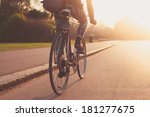 Small photo of A young woman is cycling into the sunset in the park