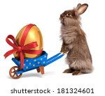 Stock photo cute easter bunny rabbit with a little blue wheelbarrow and a golden easter egg with a red ribbon 181324601