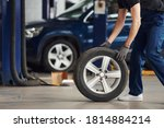 Close up view of man in work uniform with car wheel indoors. Conception of automobile service. - stock photo