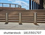 Small photo of At the foot of steps to a plaza, stainless steel bollards limit vehicular access an office building in Lower Manhattan, NYC.